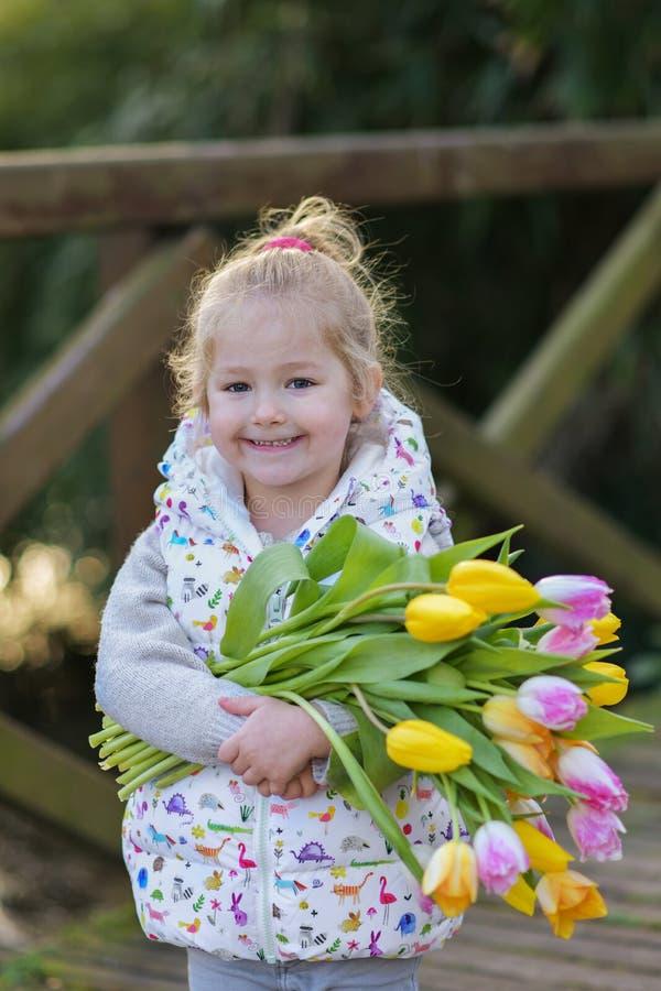 Retrato de uma menina loura com um ramalhete das tulipas em suas mãos fotografia de stock royalty free