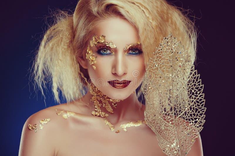 Retrato de uma menina loura glamoroso com composição dourada bonita fotografia de stock royalty free