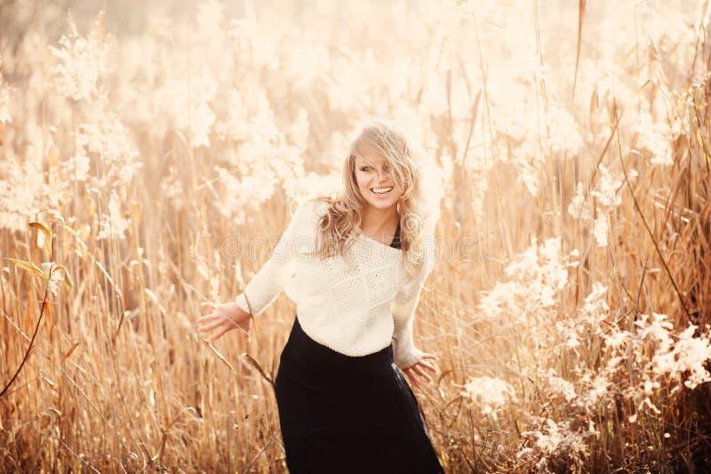 Retrato de uma menina loura nova bonita em um campo no pulôver branco, rindo imagem de stock