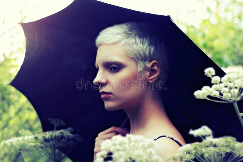 Retrato de uma menina loura nova com um guarda-chuva no prado imagens de stock royalty free