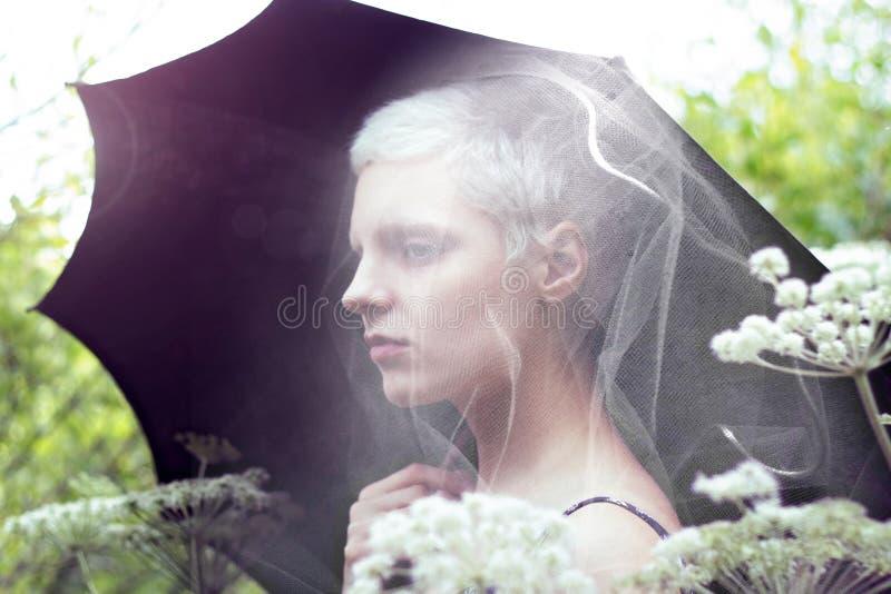 Retrato de uma menina loura nova com um guarda-chuva no prado fotografia de stock