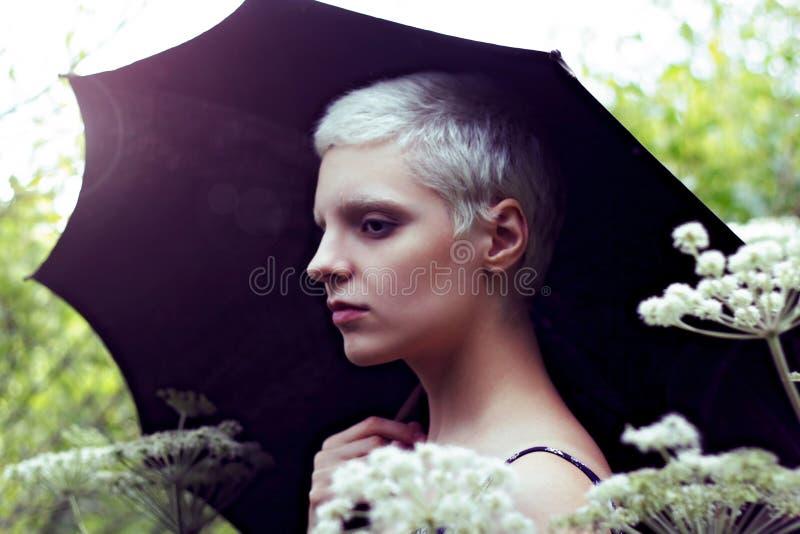 Retrato de uma menina loura nova com um guarda-chuva no prado imagens de stock