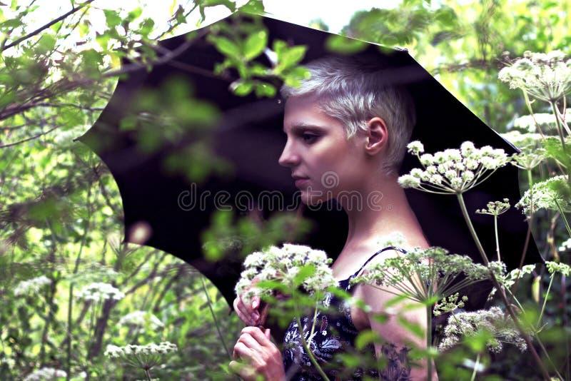 Retrato de uma menina loura nova com um guarda-chuva no prado fotografia de stock royalty free