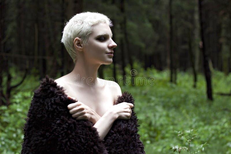 Retrato de uma menina loura nova em um casaco de pele feito nas madeiras imagem de stock