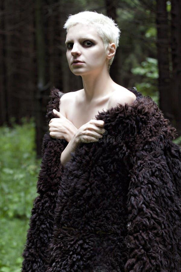 Retrato de uma menina loura nova em um casaco de pele feito nas madeiras fotos de stock
