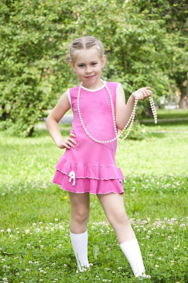 Retrato de uma menina loura nova no vestido cor-de-rosa fotografia de stock