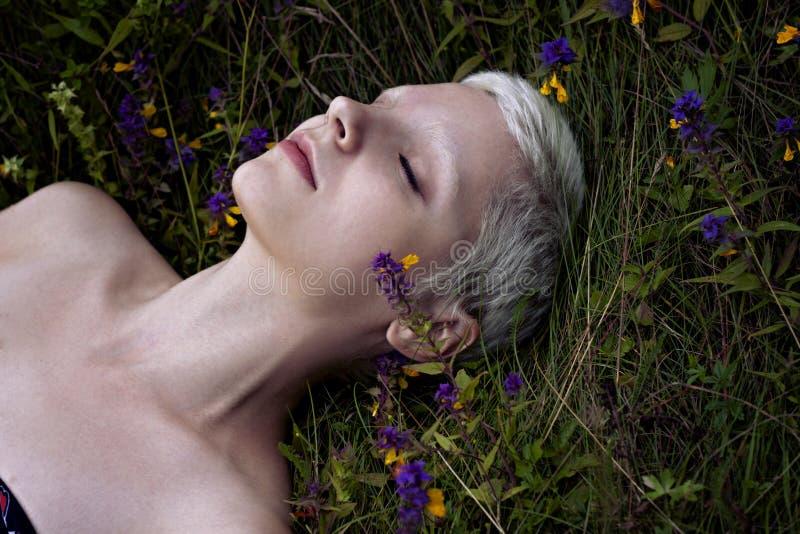 Retrato de uma menina loura nova que encontra-se em uma grama da floresta imagens de stock royalty free