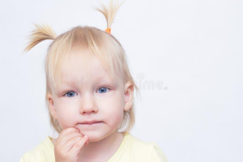 Retrato de uma menina loura de olhos azuis pequena em um fundo branco, close-up, olhando a câmera, espaço da cópia, caucasiano fotografia de stock royalty free