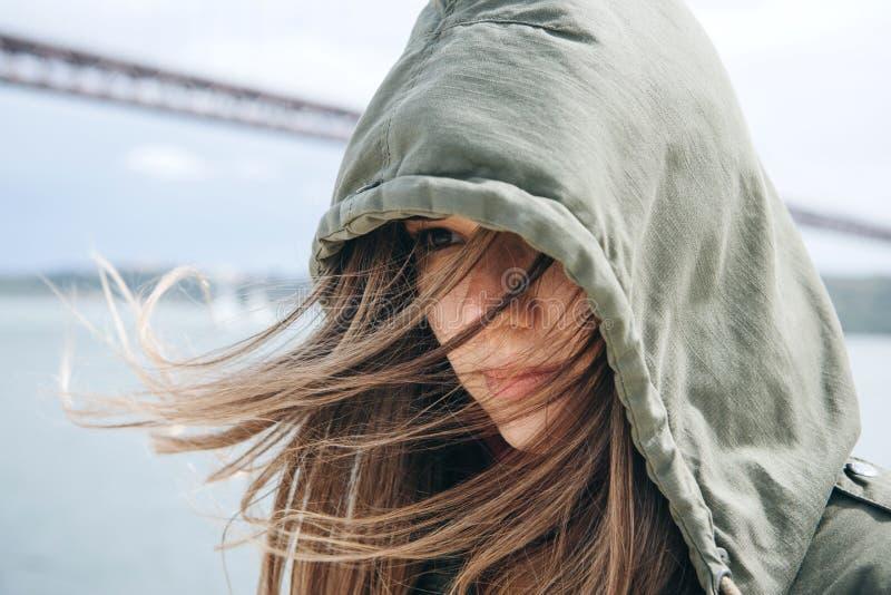 Retrato de uma menina moreno bonita com o cabelo que vibra no vento e com um olhar decidido na capa imagem de stock