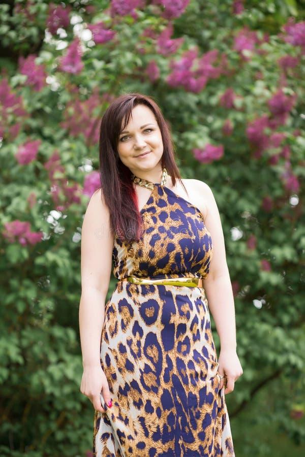 Retrato de uma menina moreno bonita sensual 'sexy' com cabelo longo no vestido amarelo-preto do leopardo que anda no parque imagens de stock