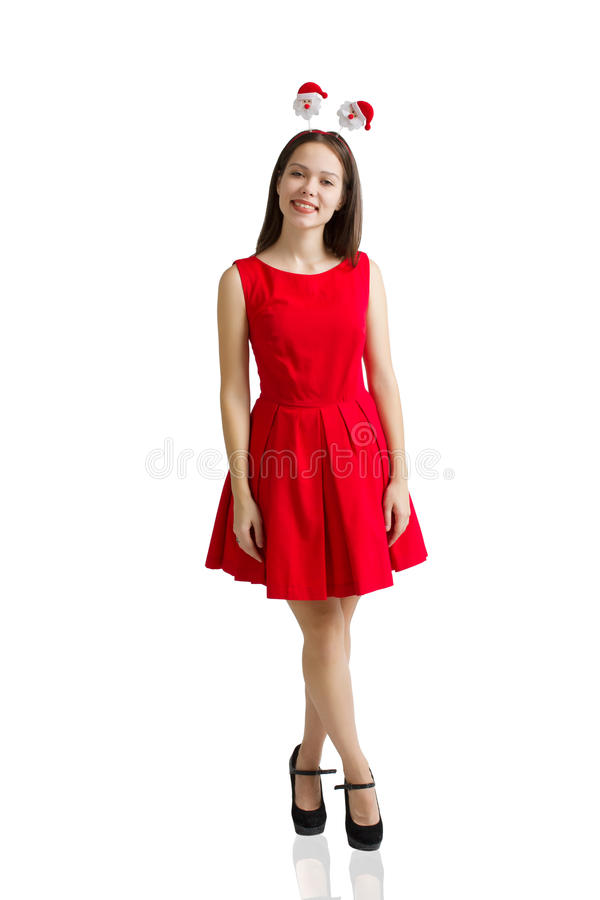 Retrato de uma menina moreno de sorriso no tiro branco do estúdio no chapéu de Santa Claus e no vestido vermelho foto de stock