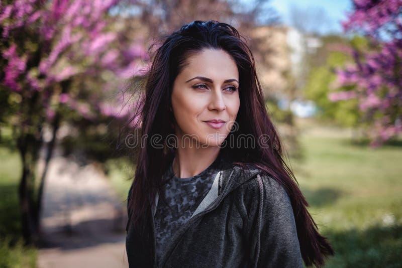 Retrato de uma menina na frente da flor de cerejeira foto de stock royalty free