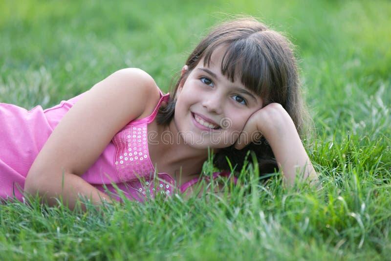 Retrato de uma menina na grama verde e na terra arrendada foto de stock