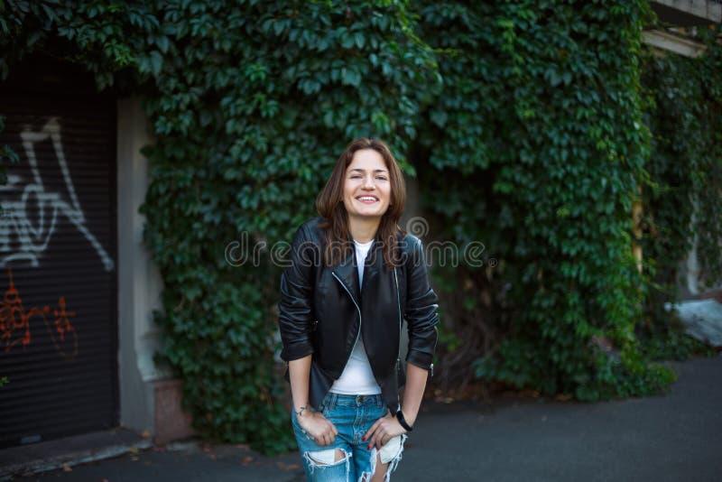 Retrato de uma menina nas calças de brim e em um casaco de cabedal, suportes contra imagens de stock royalty free