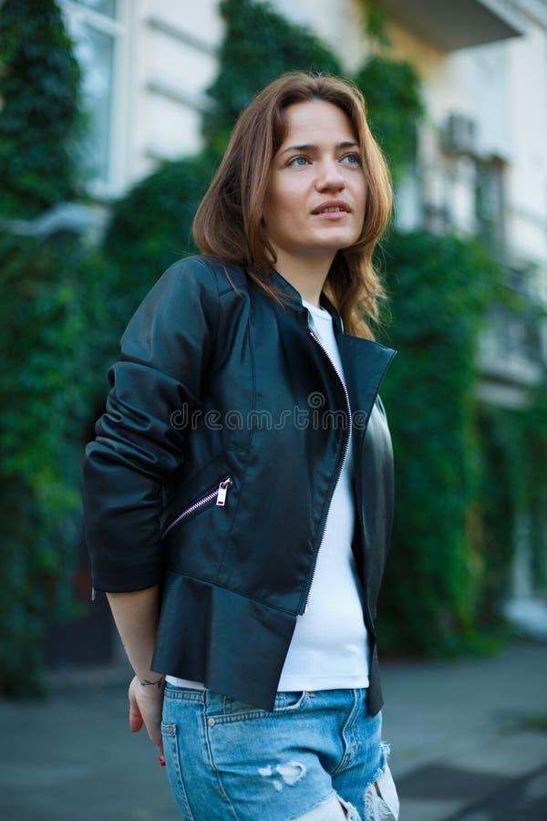 Retrato de uma menina nas calças de brim e em um casaco de cabedal, suportes contra fotografia de stock royalty free