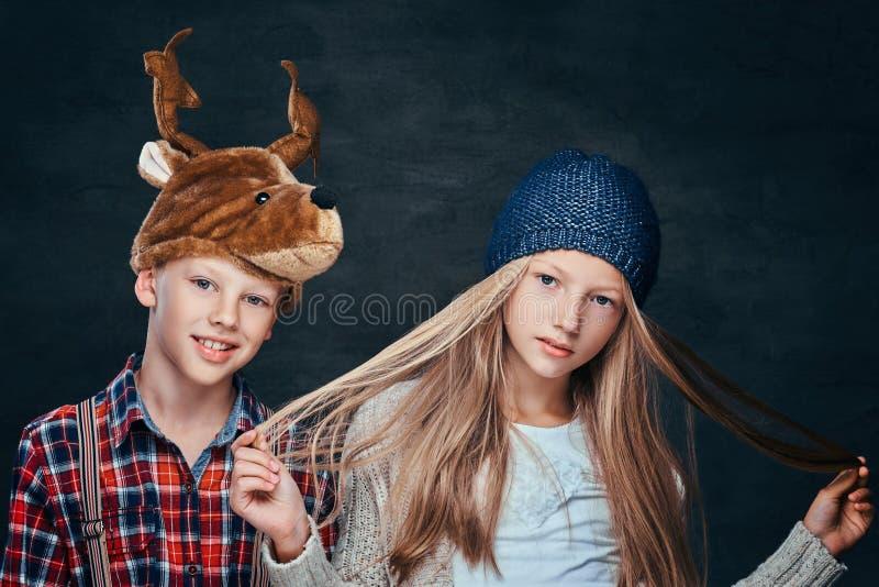 Retrato de uma menina no chapéu do inverno e no menino de sorriso no chapéu dos cervos, olhando a câmera foto de stock