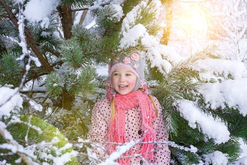 Retrato de uma menina no inverno com o sol em um chapéu forrado a pele foto de stock