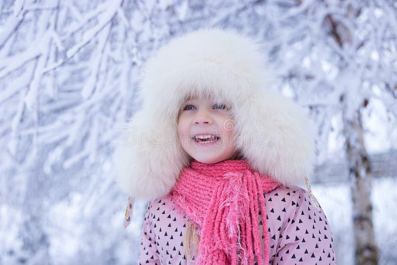 Retrato de uma menina no inverno com o sol em um chapéu forrado a pele fotografia de stock royalty free
