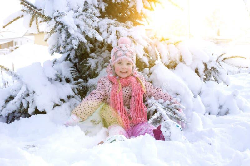 Retrato de uma menina no inverno com o sol em um chapéu forrado a pele fotos de stock royalty free