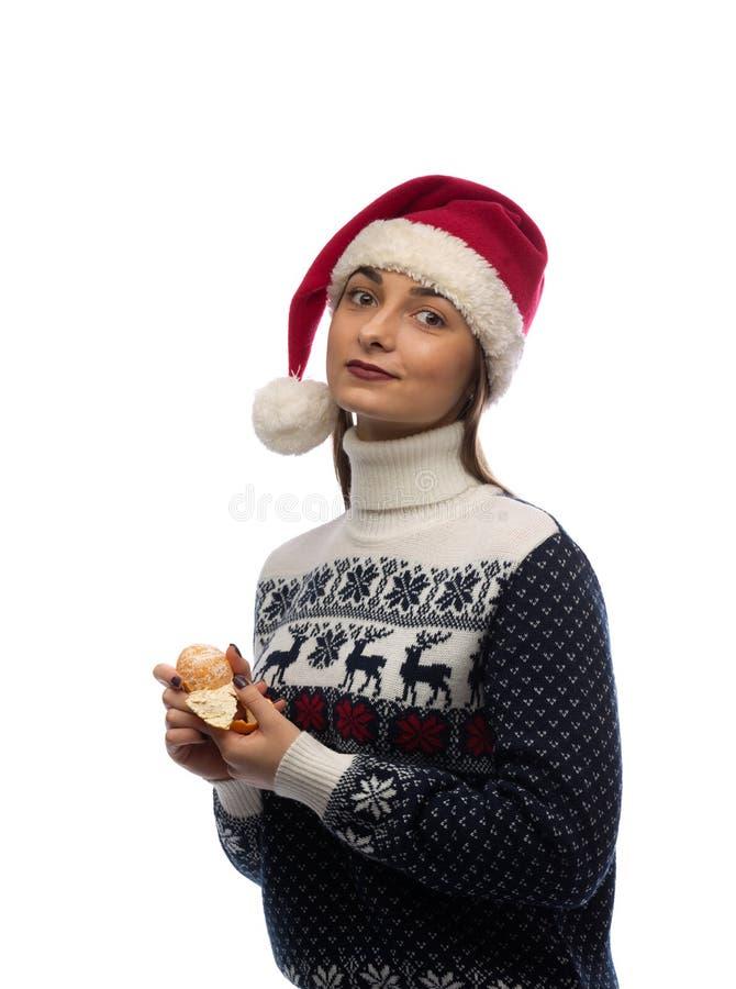 Retrato de uma menina no tampão de Santa com tangerina à disposição imagens de stock