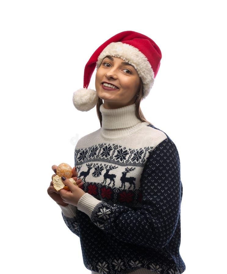 Retrato de uma menina no tampão de Santa com tangerina à disposição fotografia de stock