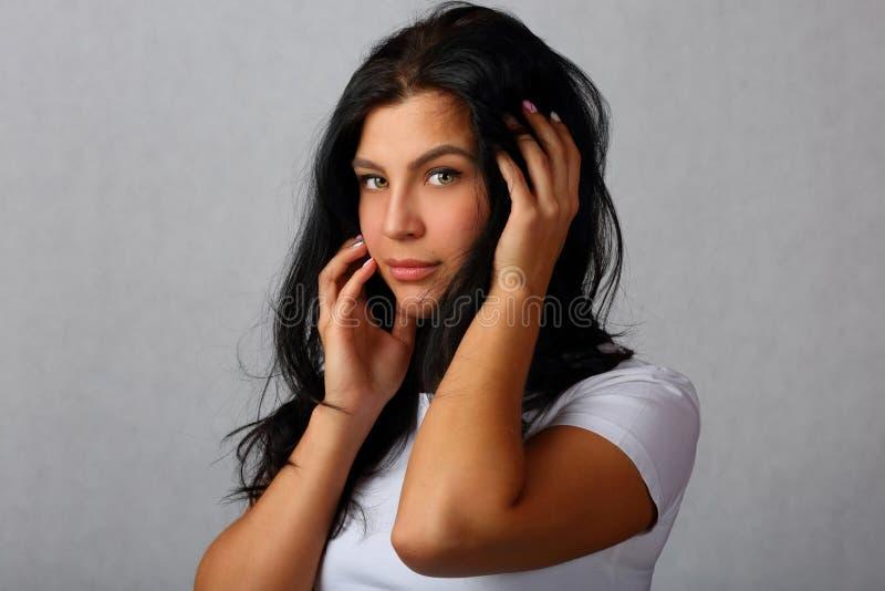 Retrato de uma menina nova, bonita em um fundo cinzento foto de stock