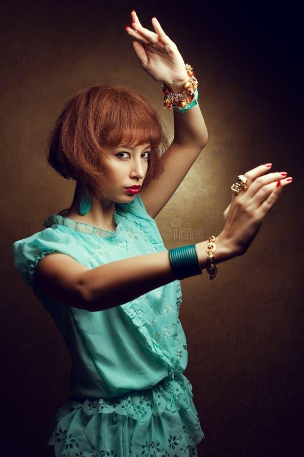 Retrato de uma menina oriental nova de oriente com posi??o elegante dos braceletes dos acess?rios na posi??o de combate e pronto  imagens de stock royalty free