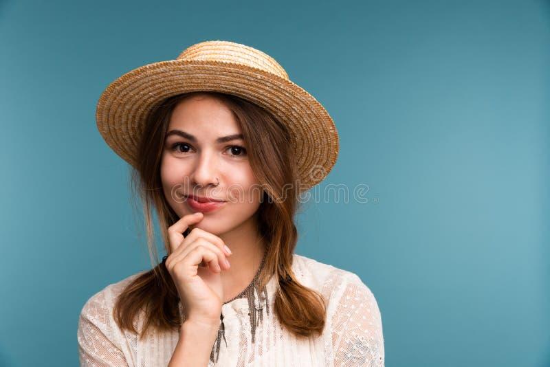 Retrato de uma menina pensativa nova no chapéu do verão isolado sobre o fundo azul fotografia de stock royalty free