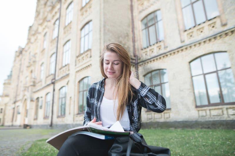 Retrato de uma menina positiva em uma camisa que senta-se em um banco perto de uma construção da universidade, lendo um livro e u fotografia de stock