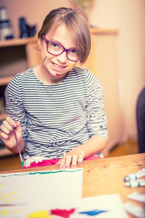 Retrato de uma menina pre-adolescente pequena do estudante que pinta em casa Foto tonificada imagens de stock
