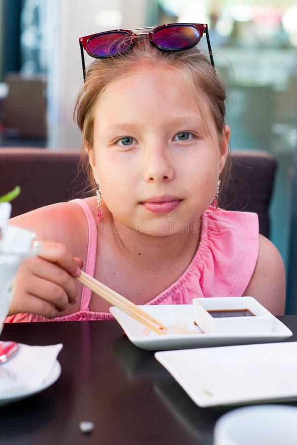 Retrato de uma menina que come o sushi no restaurante asiático fotografia de stock