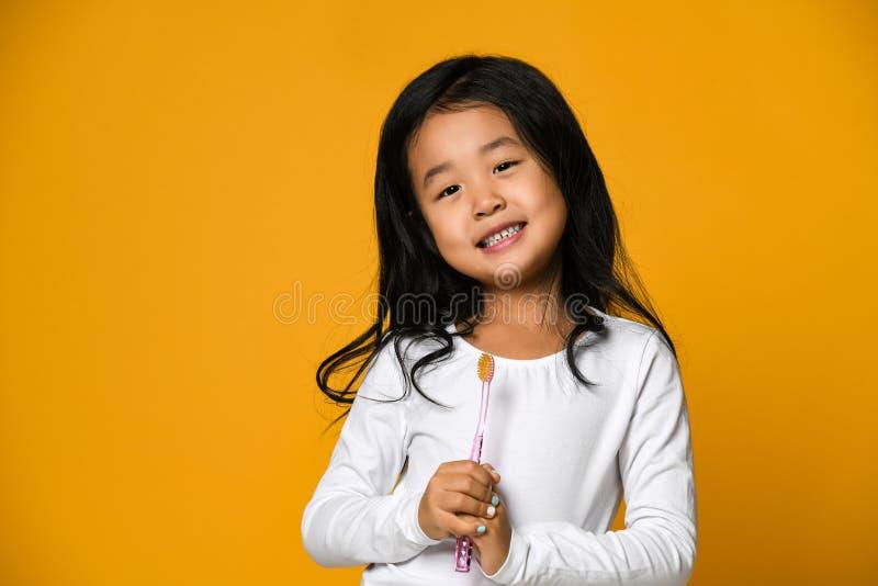 Retrato de uma menina que guarda uma escova de dentes sobre o fundo amarelo fotografia de stock royalty free