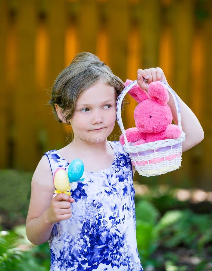 Retrato de uma menina que guarda ovos e uma cesta da Páscoa imagem de stock royalty free