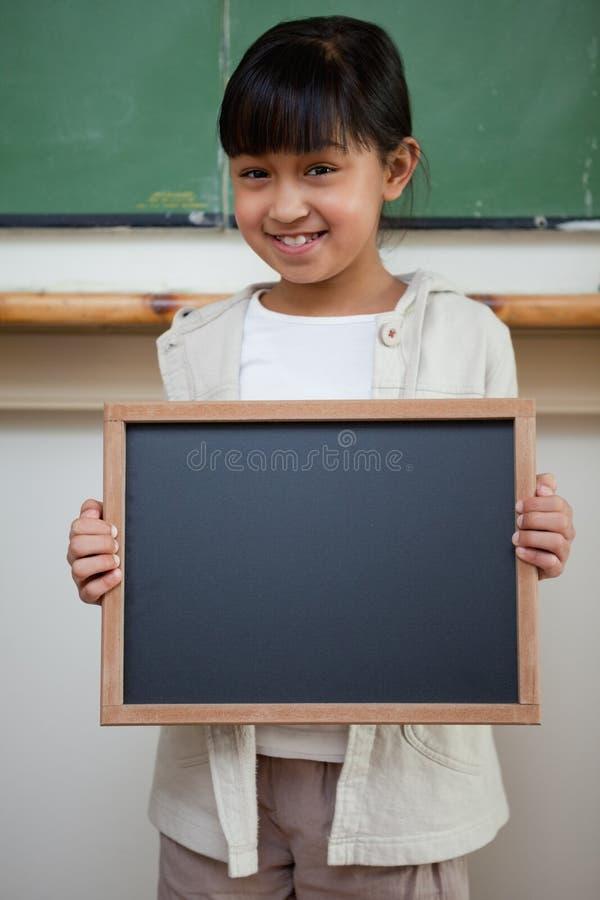 Retrato de uma menina que prende uma ardósia da escola imagem de stock