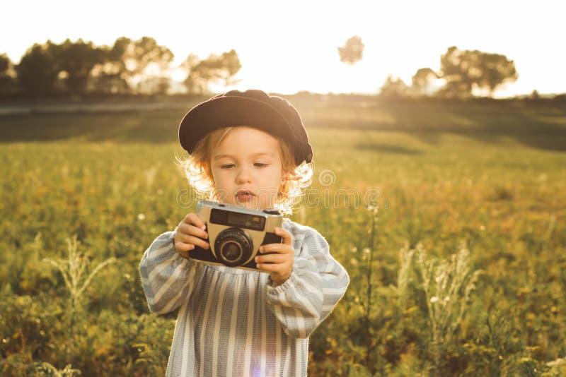 Retrato de uma menina que toma imagens com uma câmera Conceito do jogo das crianças foto de stock
