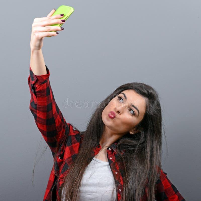 Retrato de uma menina que toma o selfie com o telefone celular contra o fundo cinzento fotografia de stock