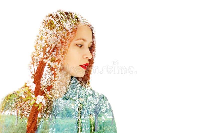 Retrato de uma menina ruivo bonita em um fundo de árvores de florescência mola do conceito imagem de stock