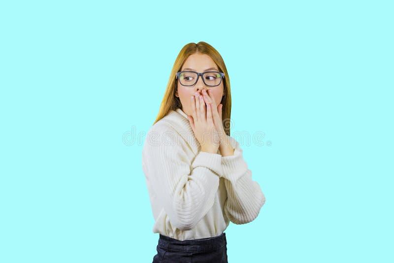 Retrato de uma menina ruivo nos vidros e em uma camiseta branca que esteja em uma metade-volta com seus braços dobrados junto imagem de stock