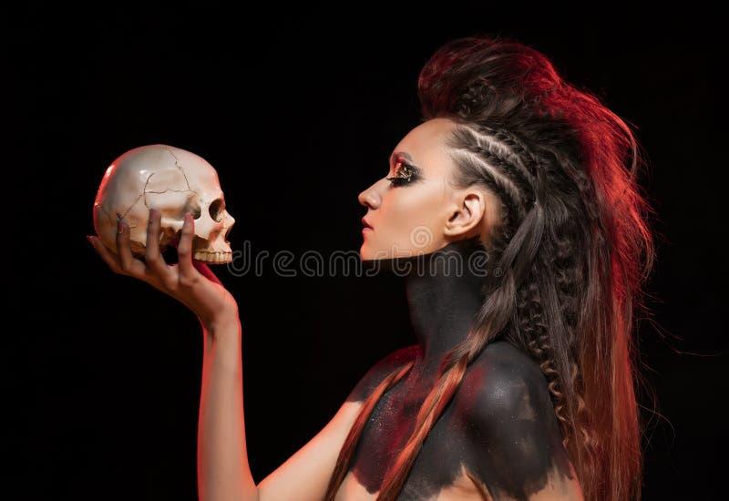 Retrato de uma menina selvagem nova que guarde um crânio em sua mão Os ombros e o pescoço despidos são cobertos com a pintura pre fotos de stock