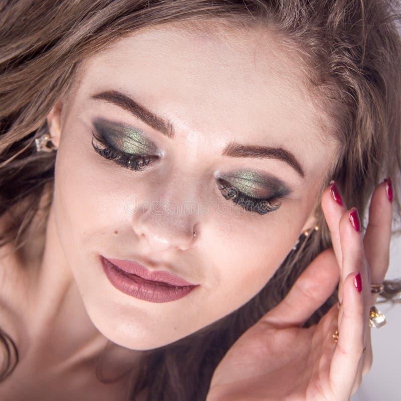 Retrato de uma menina 'sexy' bonita com olhos fechados e as pestanas longas Uma jovem mulher guarda sua mão com um tratamento de  fotos de stock