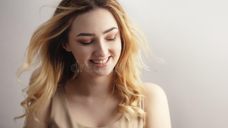 Retrato de uma menina sinceramente de riso bonita, cara com o cabelo encaracolado emaranhado do vento, o conceito do estúdio da j fotografia de stock royalty free