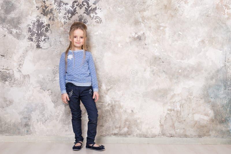Retrato de uma menina de sorriso atrativa pequena em uma camiseta azul e em calças com o cabelo dobrado em seu cabelo contra uma imagens de stock royalty free