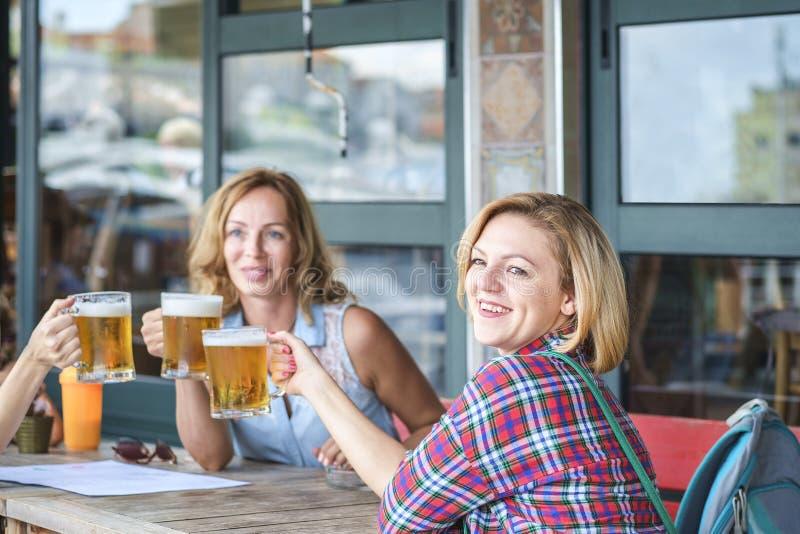 Retrato de uma menina de sorriso bonito nova que senta-se em um café com uma caneca de cerveja com seus amigos imagem de stock