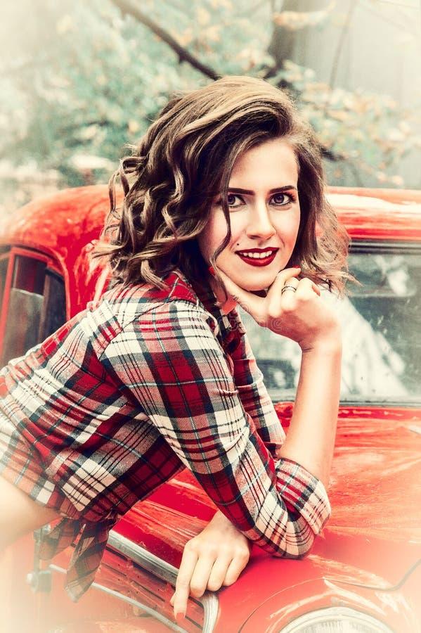 Retrato de uma menina de sorriso do pino-acima com umas belezas acima de seu bordo e uma cora em seus mordentes foto de stock royalty free