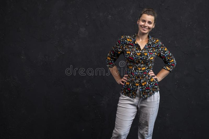 Retrato de uma menina de sorriso em um fundo preto da parede Menina caucasiano na roupa à moda da juventude Retrato do estúdio de fotos de stock royalty free