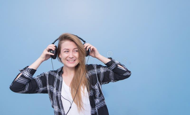 Retrato de uma menina de sorriso na roupa ocasional que está em um fundo azul, escutando a música e olhando afastado imagem de stock