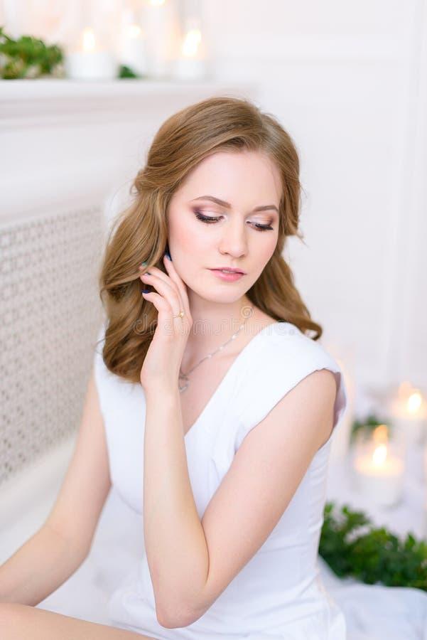 Retrato de uma menina tímida nova em um vestido limpo, sua mão que toca em sua cara delicadamente Mulher moreno nova lindo com em imagens de stock