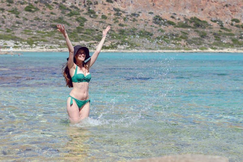 Retrato de uma moça alegre em um chapéu negro e em um roupa de banho verde que estão na água do mar esmeralda e que jogam com águ foto de stock royalty free