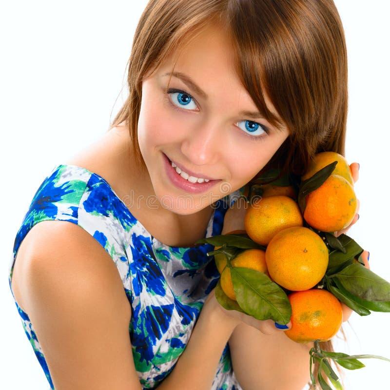 Retrato de uma moça bonita com tangerinas fotografia de stock royalty free