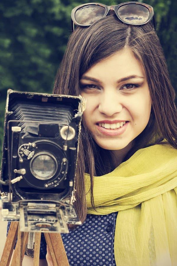 Retrato de uma moça bonita com uma câmera retro imagem de stock royalty free